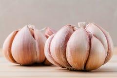 Κλείστε επάνω το οργανικό σκόρδο με την εκλεκτική εστίαση στο teak ξύλινο BA Στοκ φωτογραφίες με δικαίωμα ελεύθερης χρήσης