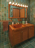 Teak bathroom in green. Small green tiled bathroom with teak vanity and mirror stock photography