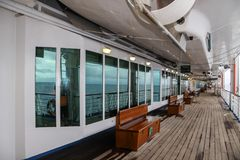 Teak bench and teak lined Promenade Deck of modern cruise ship. On a grey stormy day Stock Images