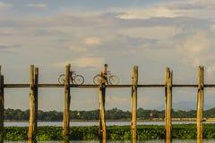 Teak bridge and two men with bikes. Royalty Free Stock Photo