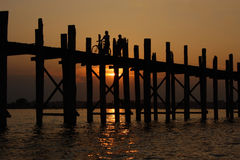 Teak bridge U Bain in Burma. Sunset, silhouettes. Stock Photos
