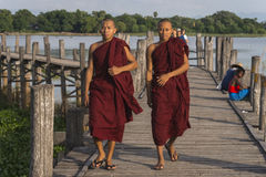 Teak bridge and walking monks Stock Photo