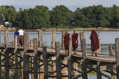 Teak bridge and walking monks Royalty Free Stock Photo