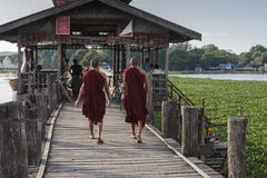 Teak bridge and walking monks Stock Image