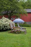Teak chairs in the garden. Two teak chairs and a parasol in a green garden Royalty Free Stock Photo