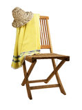Teak deck chair with towel and hat. Foldable wooden teak deck chair with towel and straw hat on a white background Royalty Free Stock Photo