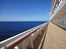 Cruise ship promenade deck. Cruise ship with beautiful wooden promenade deck in teak and stunning ocean view with clear blue sky stock photography