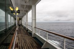 Teak lined Promenade Deck of modern cruise ship on a grey stormy. Day Stock Photography