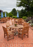 Teak patio tables and chairs on brick deck Royalty Free Stock Photo