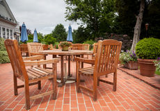 Teak patio tables and chairs on brick deck Royalty Free Stock Image