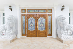 Teak wooden door with white lions statue. Teak wooden door with white  lions statue Stock Photos