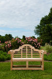 Teakholzbank oder -stuhl in der Garteneinstellung Lizenzfreie Stockfotografie