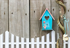 Teal blue birdhouse hanging over white picket fence. Teal blue and pink birdhouse hanging over white picket fence next to honey locust tree with wooden hearts Royalty Free Stock Image