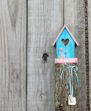 Teal blue birdhouse perched on top of post with wooden hearts Stock Photos
