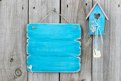 Teal blue blank sign next to blue and pink birdhouse hanging on fence