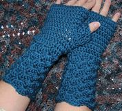 Teal Blue Crochet Fingerless Mitts. Closeup of teal blue hand crocheted fingerless mittens against a crochet background Stock Images