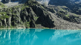 Teal Calm Body of Water Beside Rock Mountain during Day Time Royalty Free Stock Photography