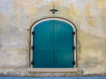 Teal Door Against a Stone Wall. A bright teal door is framed against a neutral stone wall stock photo