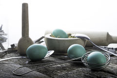 Teal Easter Eggs with spoons. Teal Colored Easter Eggs with spoons on old wood table Royalty Free Stock Images