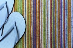 Teal Flip Flops e toalha de praia colorida Foto de Stock