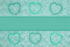 Teal frame hearts on pale teal rose plush fabric with ribbon background. Teal frame hearts on pale teal rose plush fabric background with ribbon to provide copy stock image