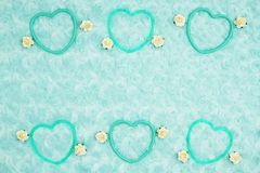 Teal frame hearts and rose buds on pale teal plush fabric background. Teal frame hearts and rose buds pale teal plush fabric background with muted mix of shades stock photography