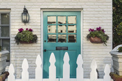 Teal front door of a classic home. A teal wooden front door to a home, with white picket fence gate in foreground. The door is framed by two flower planters, and Royalty Free Stock Photography