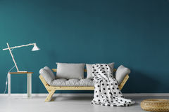 Teal painted living room. With spotty blanket, modern lamp, and a small table Royalty Free Stock Image