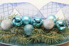 Teal Christmas Decorations. Teal and silver christmas decorations on top of a layer on fresh cut pine branches. The background is curled blue and sliver ribbon Stock Photos