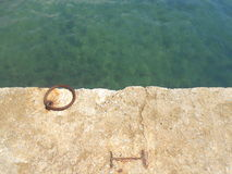 Teal waters and an iron ring in a dock. Capture of an iron ring bolted on the light concrete docks of Nea Kallikrateia, a small seaside village in northern royalty free stock image