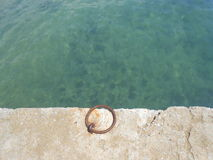 Teal waters and an iron ring in a dock. Capture of an iron ring bolted on the light concrete docks of Nea Kallikrateia, a small seaside village in northern stock image