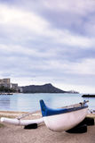Teal and white fiberglass outrigger canoe. With ama for balance in Waikiki, with Diamond Head in the background stock photo