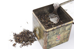 Tealeaves in antique tea box. Himalayan tea leaves in old chinese tea box with antique silver teaspoon and some tealeaves on the side Stock Photo