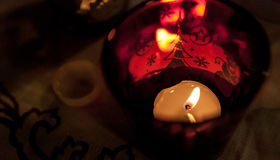 Tealight candle in a red Christmas candle cup, subdued light. Stock Images
