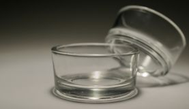 Tealight Cup Holders. Empty glass tealight holders against a gradient black and white background stock image