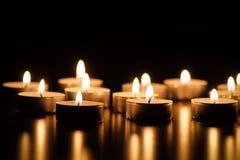 Tealight stearinljus i mörkret arkivfoto