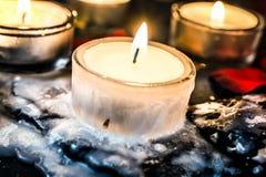Tealights στην πλάκα με το κερί γύρω από το φως τσαγιού που μοιάζει με τον πάγο Στοκ Φωτογραφίες