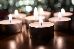 7 Tealights romântico para o jantar na tabela de madeira com o Bokeh na noite Imagem de Stock