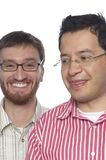 Team 01. Close up of two men facing camera one Caucasian, the other Latino wearing glasses and making expressions against a white background Stock Image