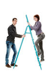 Team. Guy holding the ladder on which to climb up the girl, isolated on a white background Royalty Free Stock Images