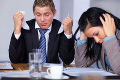 Team of 2 stressed and depressed business people. Sitting at conference table, negotiation failure or bankrupcy concept Royalty Free Stock Photos