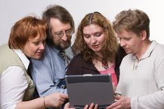 Team. Of four different aged business people looking at screen of notebook on white background Stock Photo