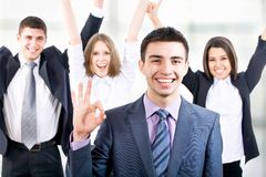 Team. Portrait of business men showing ok sign with cheerful team in background Royalty Free Stock Photo