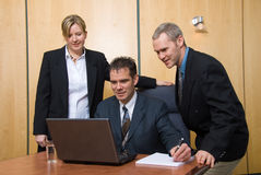 Team of 3. 3 business people around a laptop in a meeting royalty free stock image