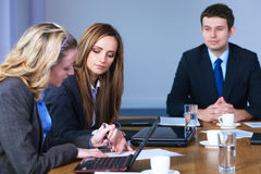 Team of 3 business people sitting at table. Team of 3 business people sitting at conference table during meeting Royalty Free Stock Photo