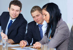 Team of 3 business people work on some paperwork. Team of 3 young business people work on some documents, all sitting at conference table Royalty Free Stock Image