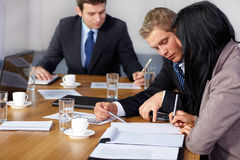 Team of 3 business people working on calculations. Team of 3 business people working on some calculations, calculator and some documents on table Royalty Free Stock Image