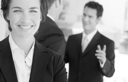 Team. One business woman staring at camera while two businessmen talk in background Royalty Free Stock Photo