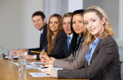 Team of 5 business people. Sitting at conference table with blonde businesswomen on the foreground Stock Photos