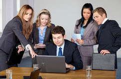 Team of 5 business people during meeting. One men sitting and work on the laptop while other make some remarks Royalty Free Stock Image